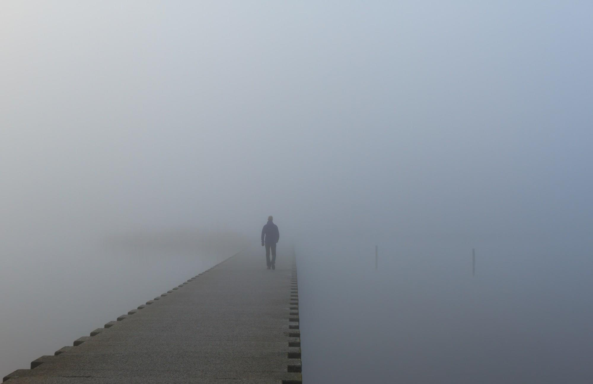 Man on a jetty walking into the dense fog.