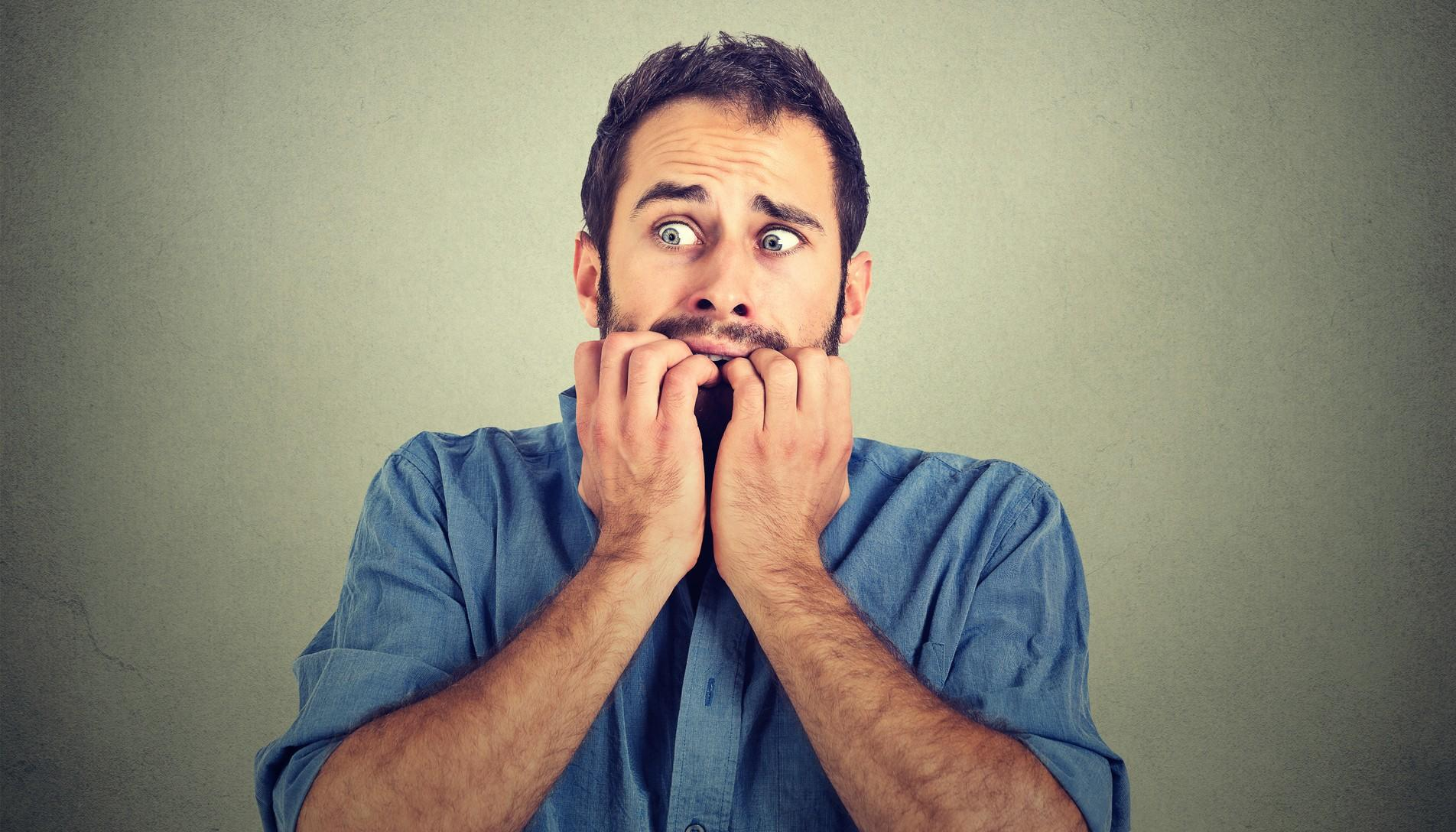 Portrait anxious young man biting his nails fingers freaking out