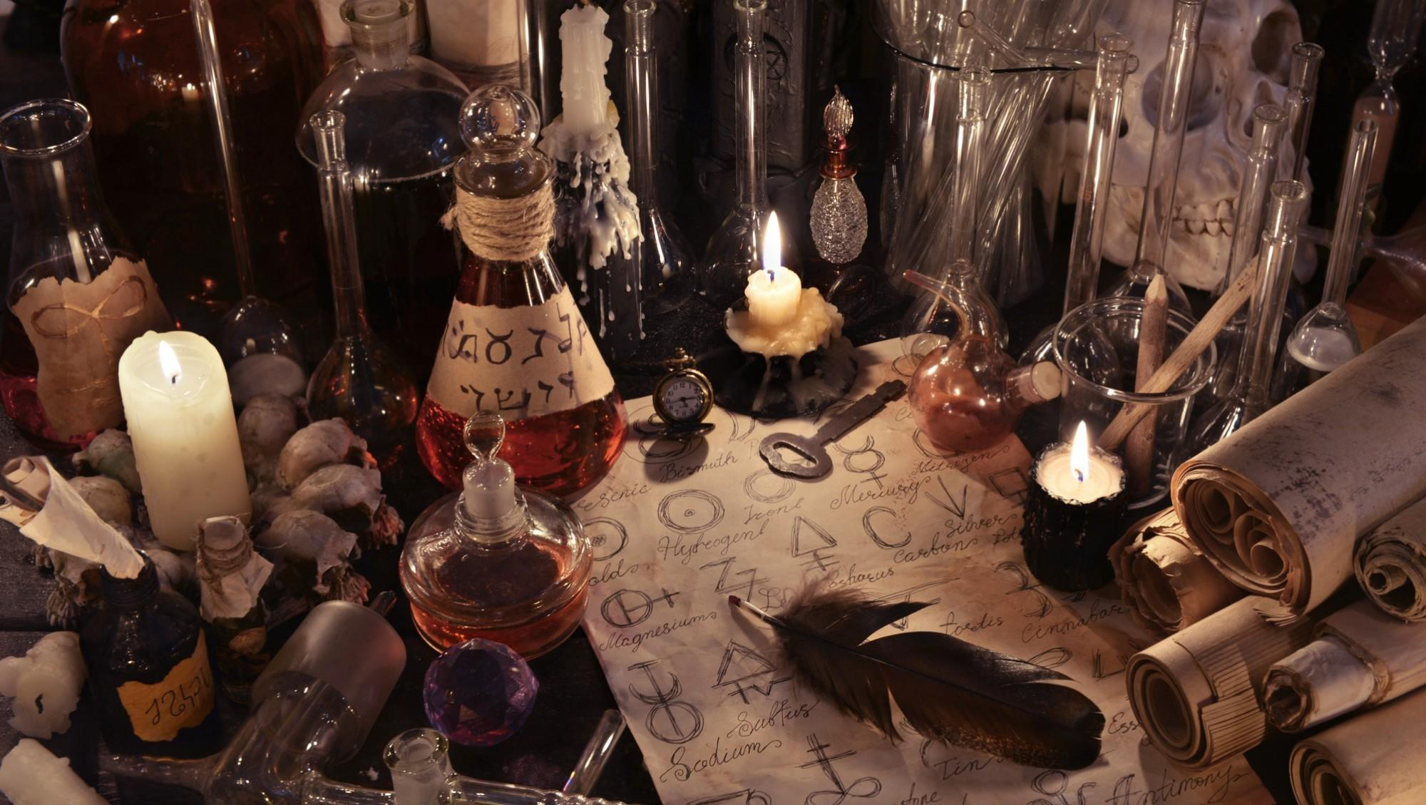 Still life with alchemy paper, bottles and candles