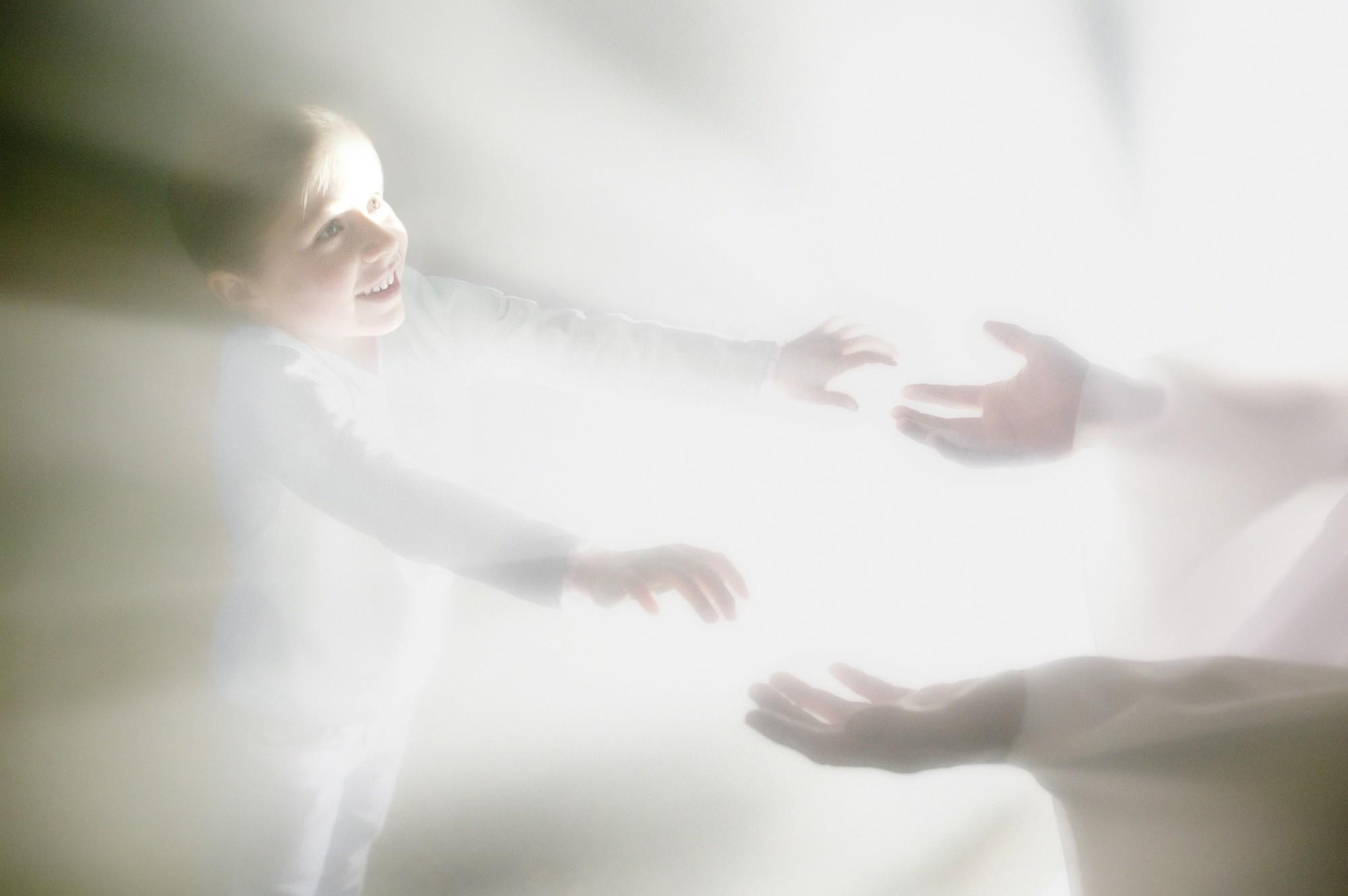 Boy reaches for hands of an angel
