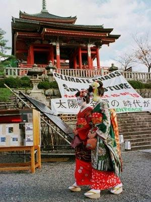 """Traditional Japanese dancers, know as Maiko, walk in front of a big banner that reads """"Climate Chaos or Solar Future, The choice is Over..."""" set up by the Green Peace for their campaign against the UN Conference on Global Warming at Kiyomizu Temple in Kyoto, Sunday, Nov. 30, 1997. The international conference to promote the reduction of CO2 and limit the use of energy was discussed by representatives from major nations here."""
