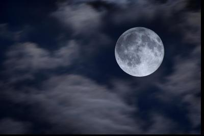 A full moon visible through clouds. On the next page you can see an image of Jupiter appearing from behind the moon.