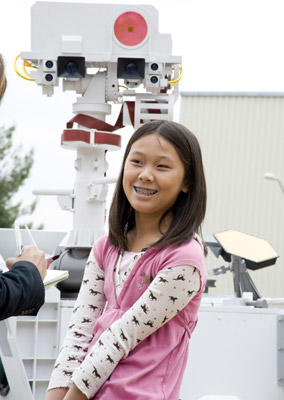 As a name, Mars Science Laboratory is descriptive but hardly catchy. Through a contest, NASA enlisted the help of more than 9,000 students in naming the rover. The winner was 12-year-old Clara Ma of Lenexa, Kan., shown here in front of a model of the craft. She picked a fitting name that encapsulates both the rover's scouting ability and the human impulse that's sending it to Mars: Curiosity. Next, see the Jet Propulsion Laboratory. As part of the prize Clara was able to write her name on the rover, can you guess where?