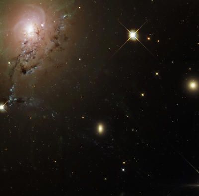 The pinwheel of dust at the upper left is an elliptical galaxy sliding toward the central black hole inside Perseus A. Space dust is generally drawn into orbit around nearby massive objects like black holes, stars and planets.  Click ahead to see a nearby nebula in the Perseus cluster.