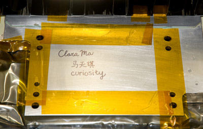 """As part of her award for selecting the name of the Mars Science Laboratory rover, Clara Ma got to visit the Jet Propulsion Laboratory in Pasadena, Calif. in June 2009. She entered the clean room where Curiosity is being assembled, and signed her name on the belly pan of the rover. Between """"Clara Ma"""" and """"Curiosity,"""" she wrote her name in Chinese: Ma (horse) and two characters that mean Jade from Heaven. What do you think Curiosity's face looks like?"""