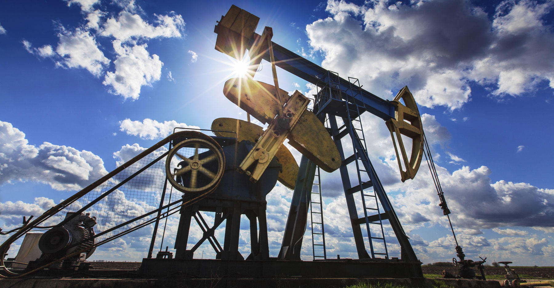 Operating oil and gas well profiled on cloudy sky