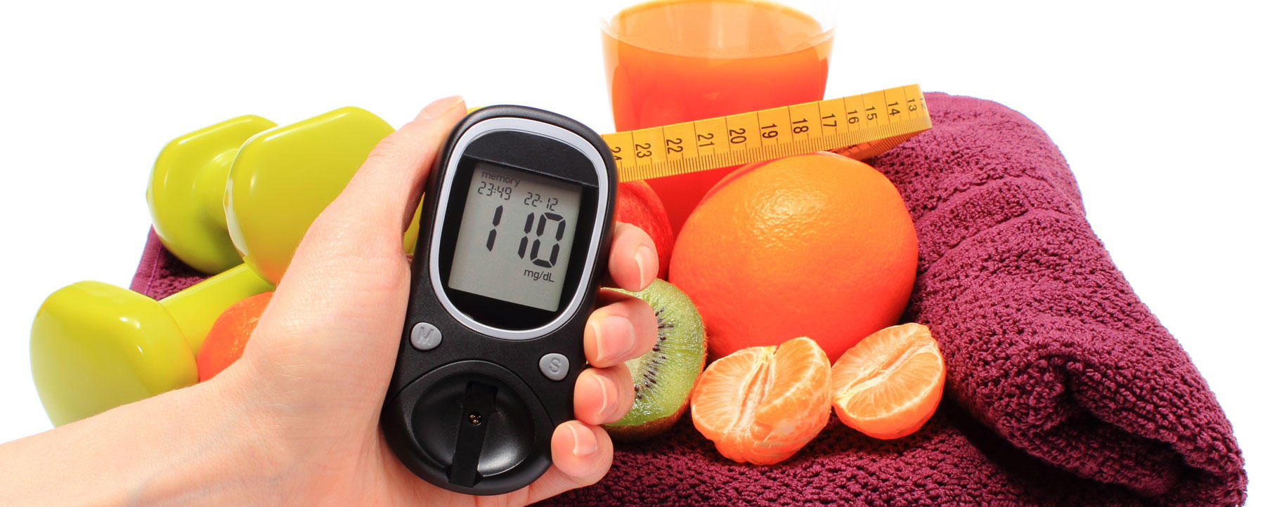 Hand with glucometer, fruits, tape measure, juice and dumbbells
