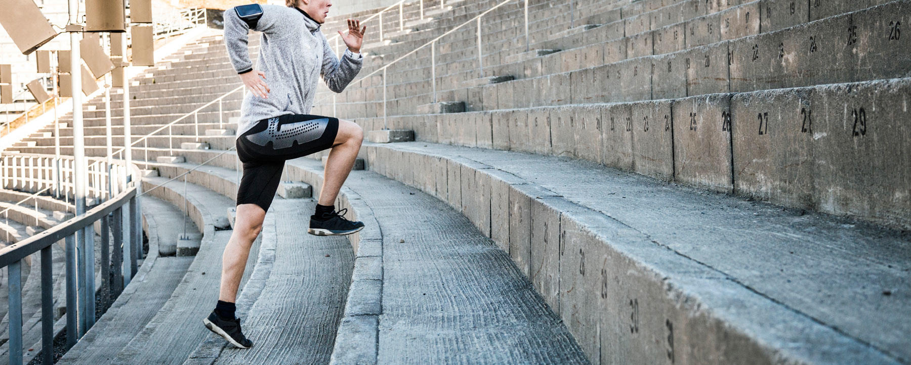 Young man exercising in early morning running on steps