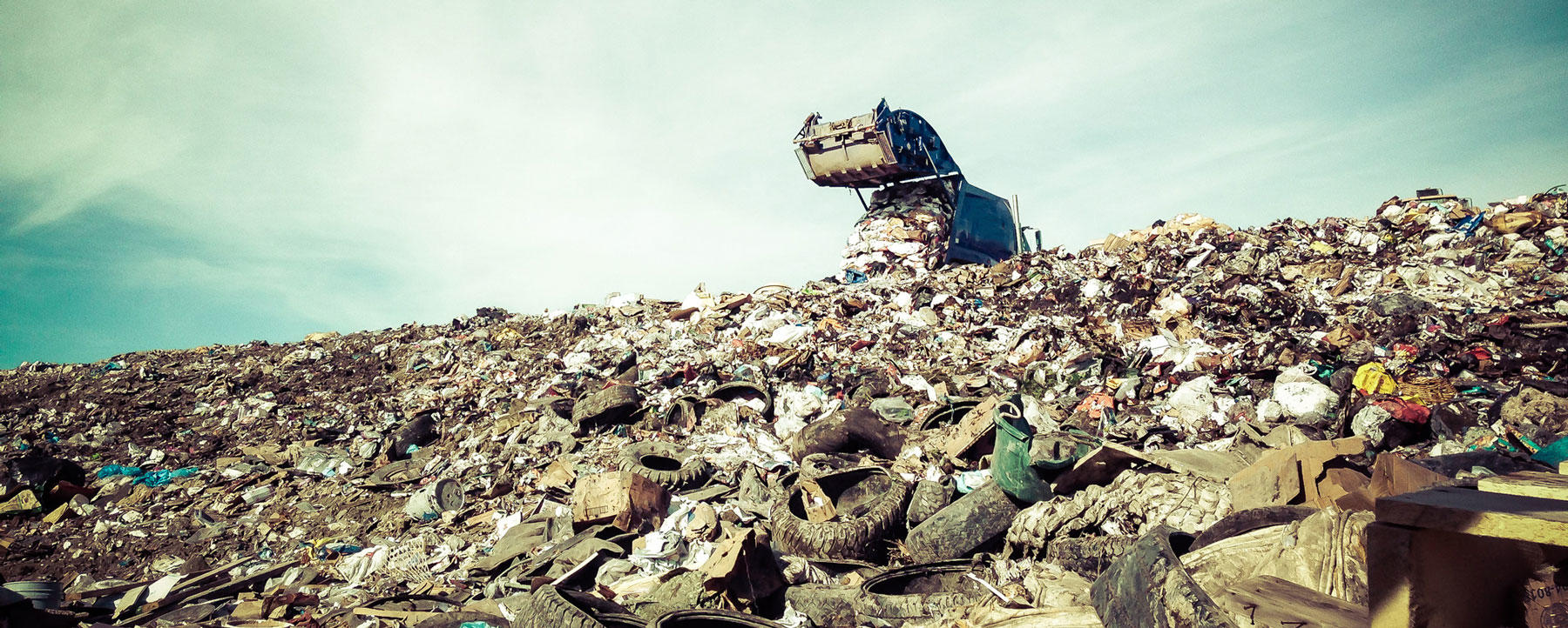 Garbage trunk dumping waste on landfill