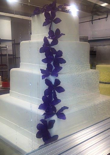 A four-tiered cake with purple flowers, seen at Lackawanna.