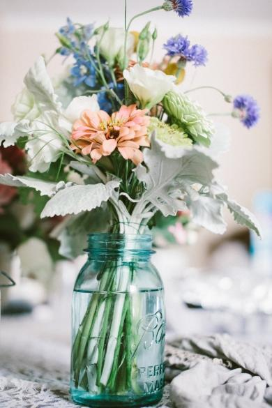 Flowers become country vintage chic when arranged effortlessly in a blue Mason jar.