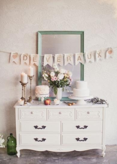 A bridal shower's dessert offerings are displayed on a rustic wooden chest of drawers.