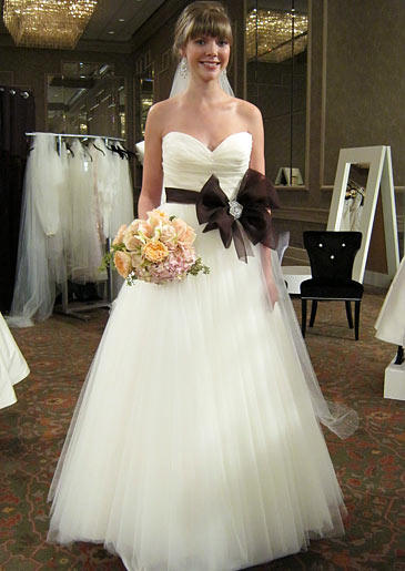 A bride's ballerina-inspired tulle ball gown is cinched at the waist with an oversized chocolate bow.
