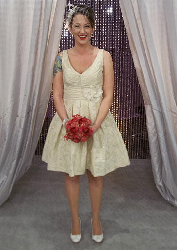 A champagne brocade short dress with plunging V-neck and flower detail at the waist is vintage chic.