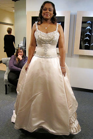 A buff-colored ball gown has braided and beaded straps that support a gentle scoop neckline.