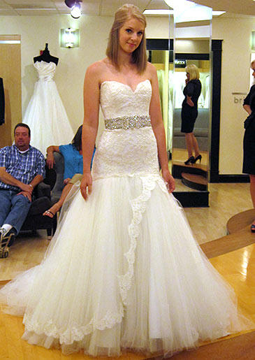 This white lace and tulle gown toes the line between sweet and sexy with its full skirt and curve-hugging bodice.