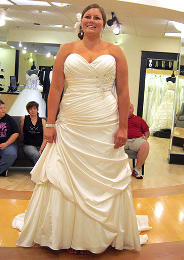 This ivory A-line wraps around the bride's body and has pickups at one thigh to elongate and slim the figure.
