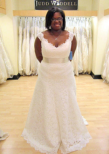 These delicate lace cap sleeves add youthfulness to a formal lace A-line gown with an ivory sash at the waist.