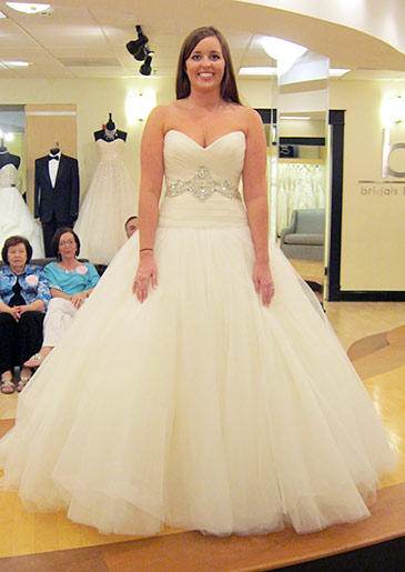 The dropped waist on this ball gown makes the style slightly more contemporary; crystal beadwork at the waist eliminates the need for too many bridal accessories.
