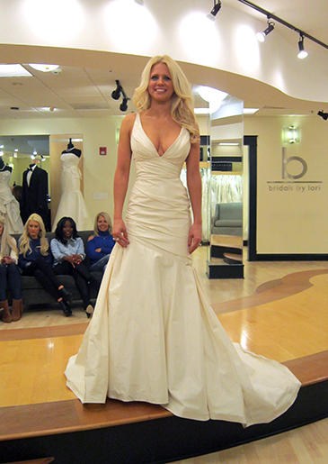 This low-cut ivory fit and flare has a V-neck and ruching through the bodice.