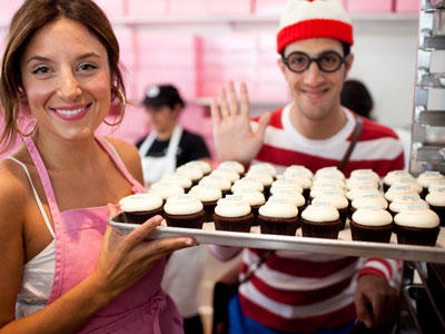 Katherine displays a tray of cupcakes while Waldo waves. Or maybe he's just waiting to snatch a cupcake?
