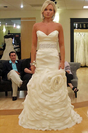 Pamela wears Rivini Style Camelia.  Fabric: silk satin organza/silk double organza  Description: dropped waist with sash and floral skirt  Color: ivory  Price: $$$$$
