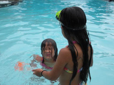 Alexis and Hannah cool off in the pool on a hot day.  Spending time by the water at a pool, beach or water park is a great way to play outside without overheating.