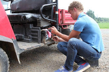 Jeremy Roloff, one of the twins, fixes a tractor.  As one of the oldest and tallest members of the Roloff family, it is his job to drive the tractors filled with pumpkin seekers each fall.