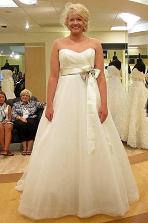 Megan wears Amsale Style Sabrina.  Fabric: tulle  Description: ball gown with side ruched bodice, satin sash  Color: ivory  Price: $$$$