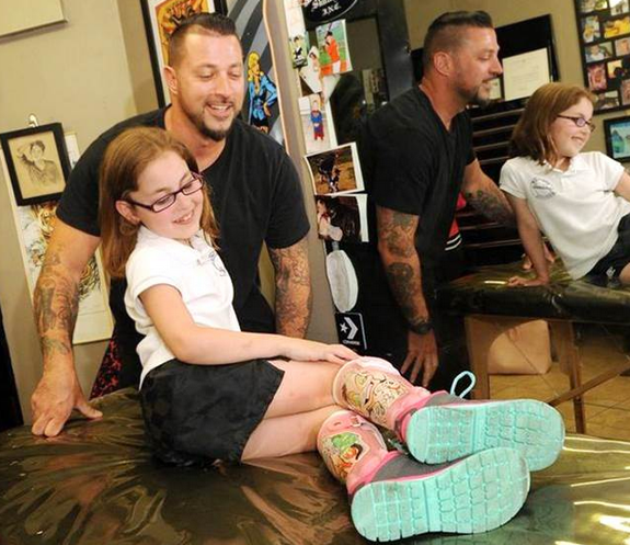 tattoo artist with girl with leg braces