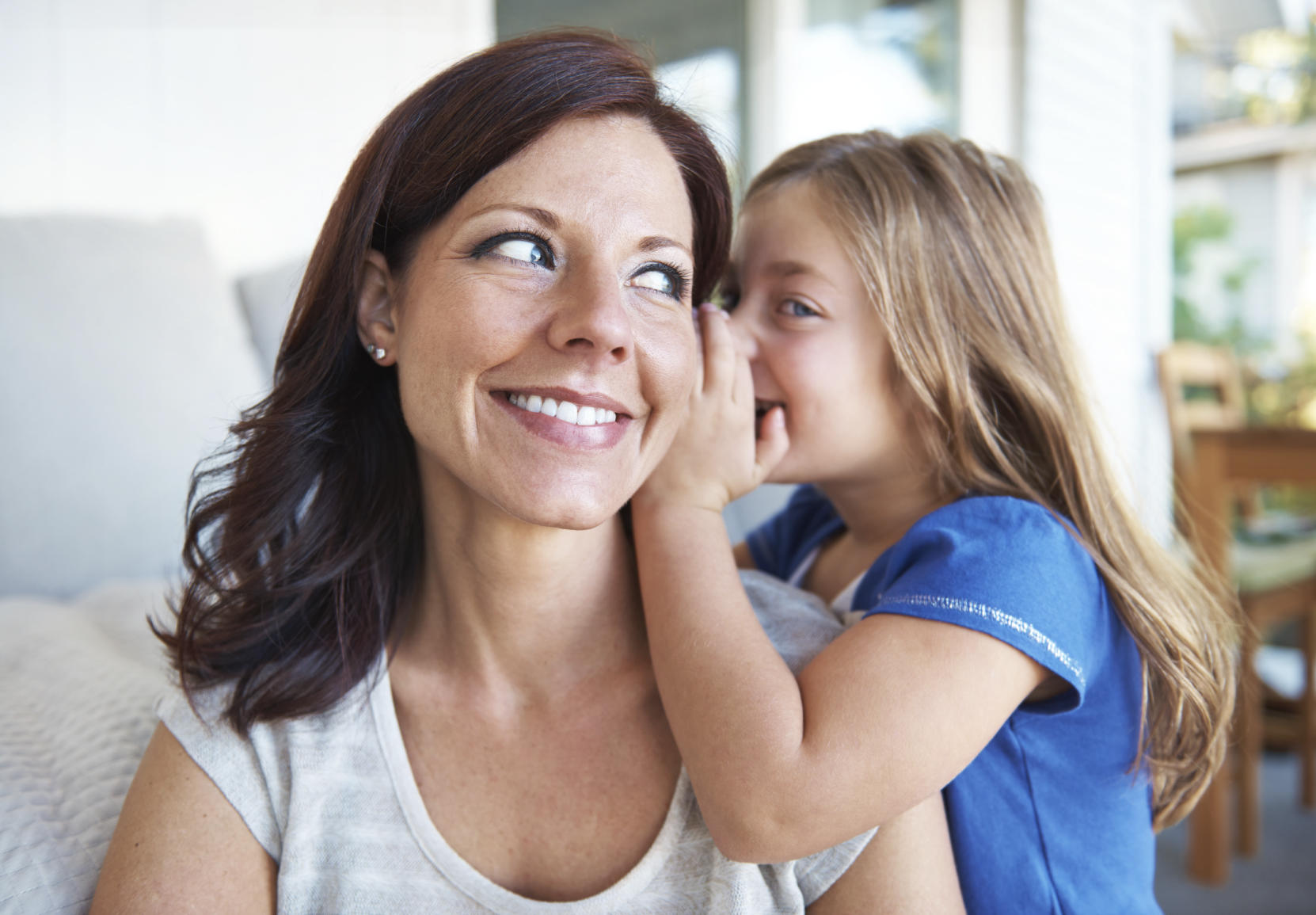 Shot of a cute little girl whispering into her smiling mother's ear