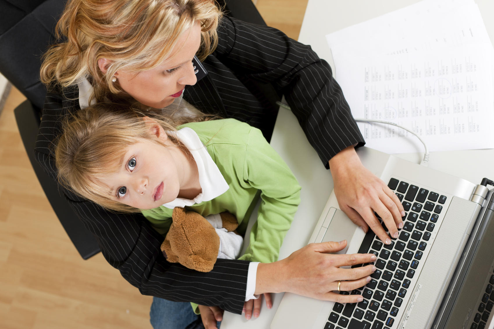 A child sits on her mother's lap as the mother works on a computer