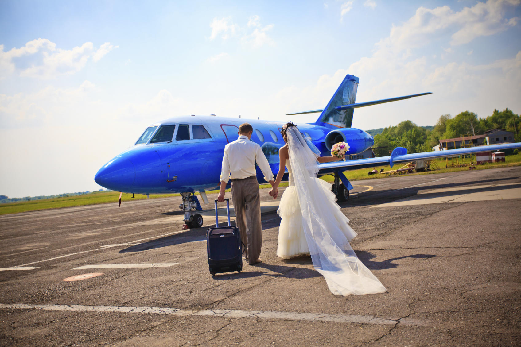 picture of a bride and groom boarding an airplane