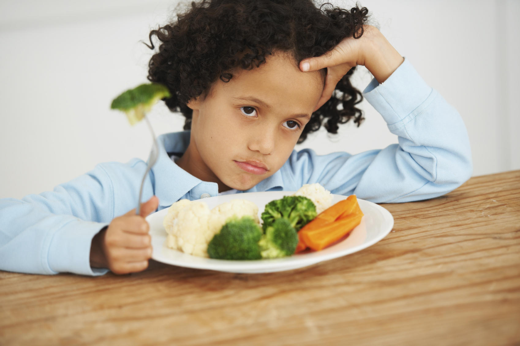 kid glumly sitting in front of a plate full of vegetables