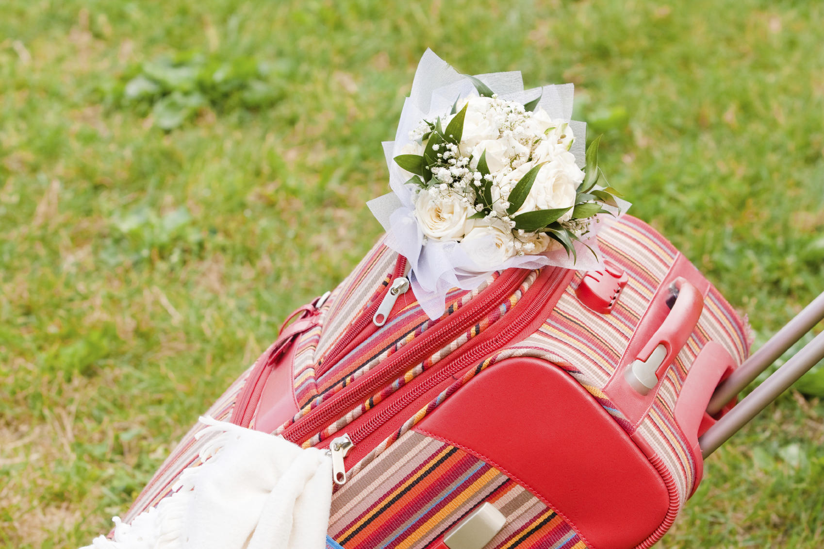 Packed suitcase with bridal bouquet and white planket is ready for honeymoon