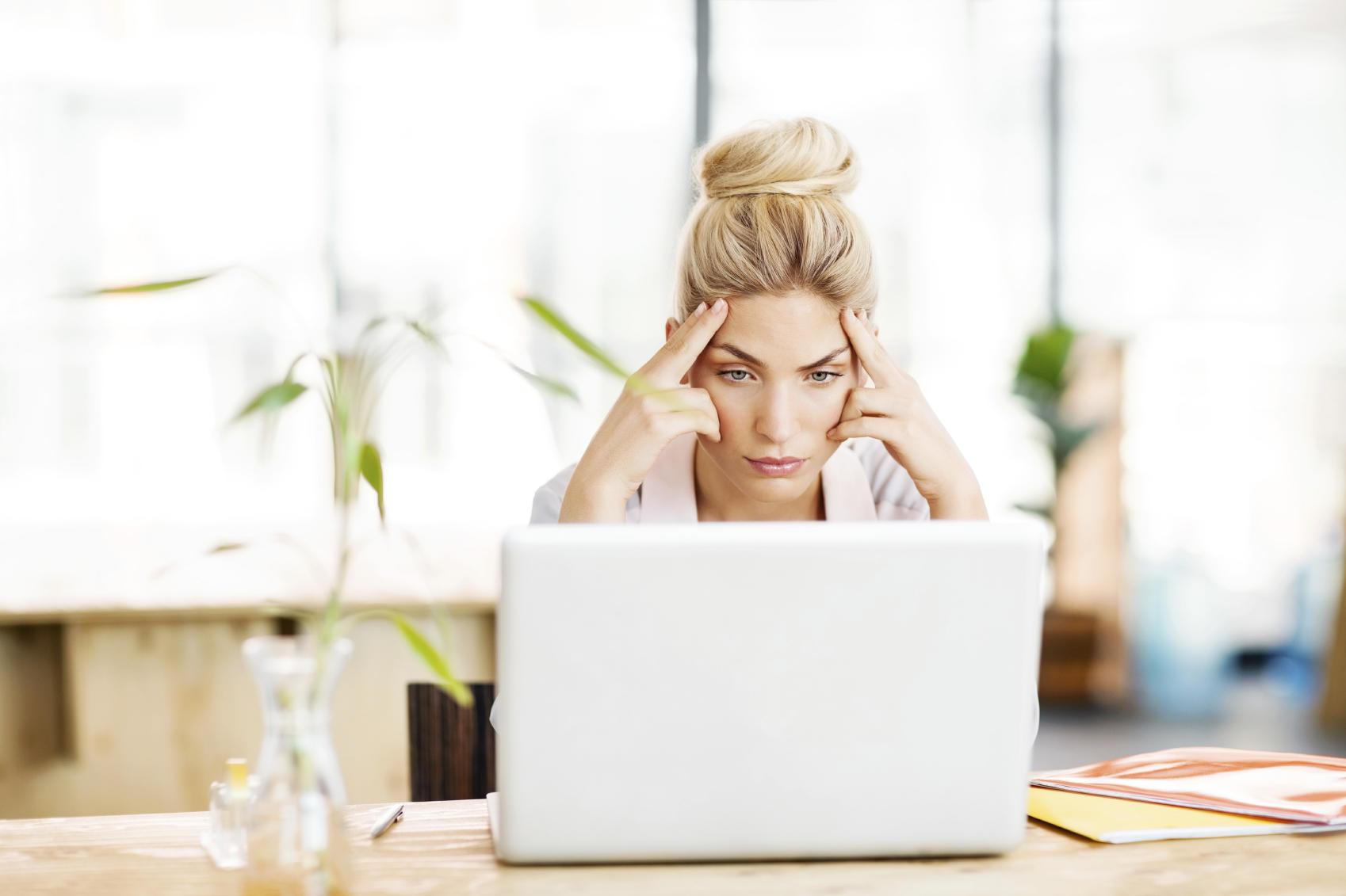 Worried Female Entrepreneur Looking At Laptop