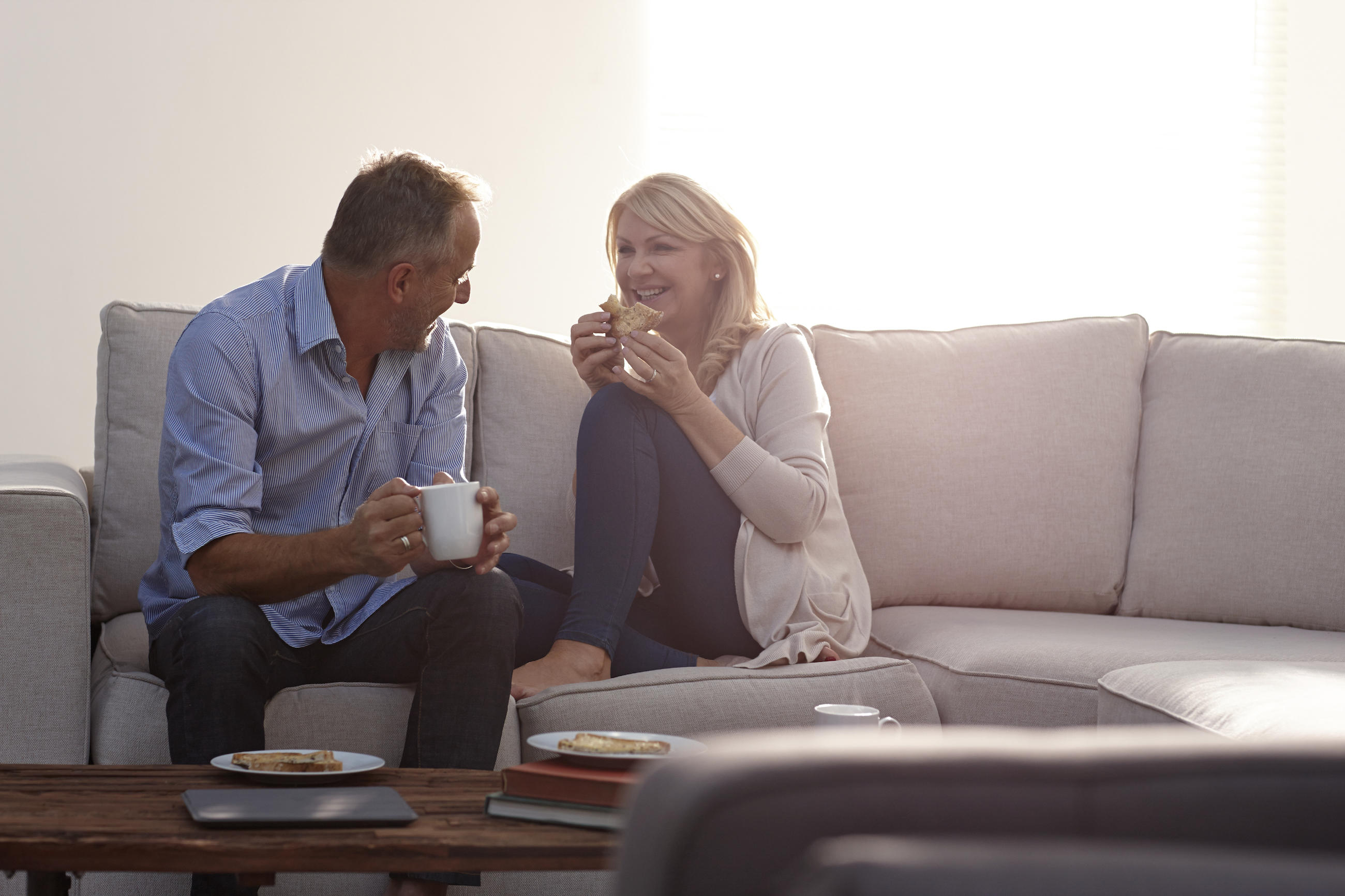 Smiling mature couple having coffee on sofa