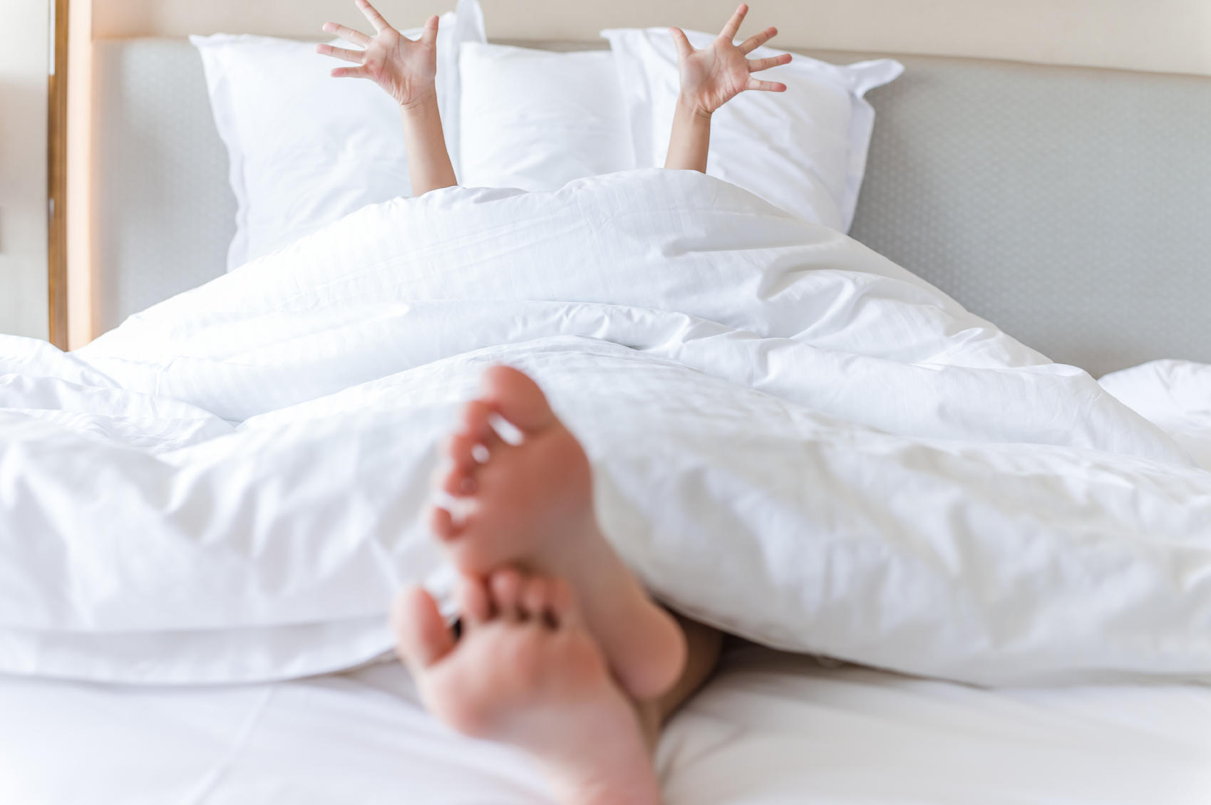 Person Sleeping on Bed Raising Hands