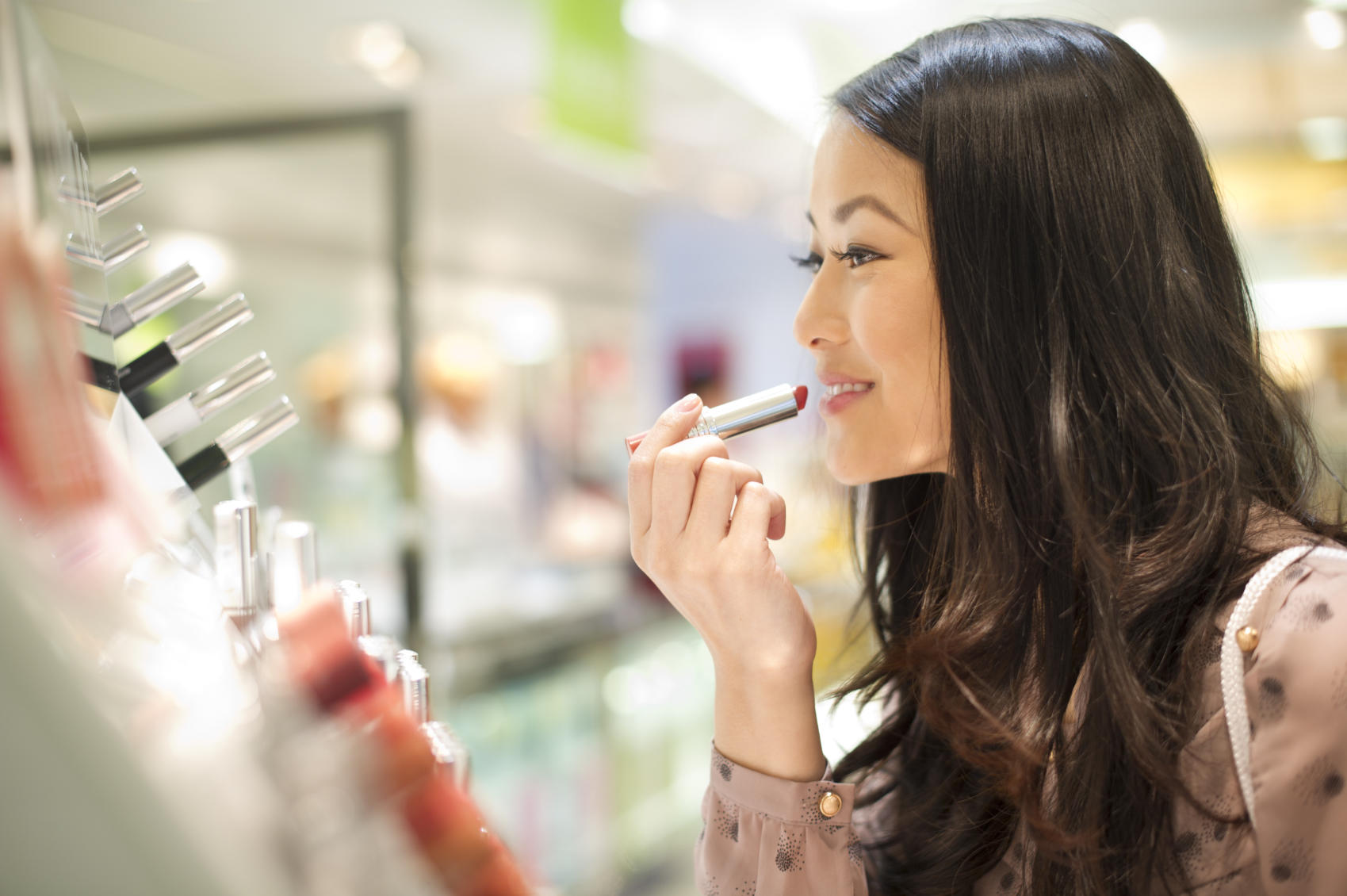 Woman applying lipstick in store