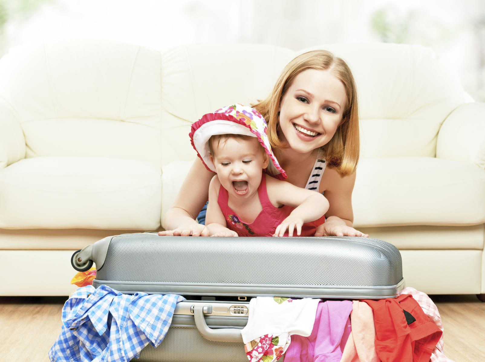 Mother and baby girl with suitcase and clothes ready for traveli