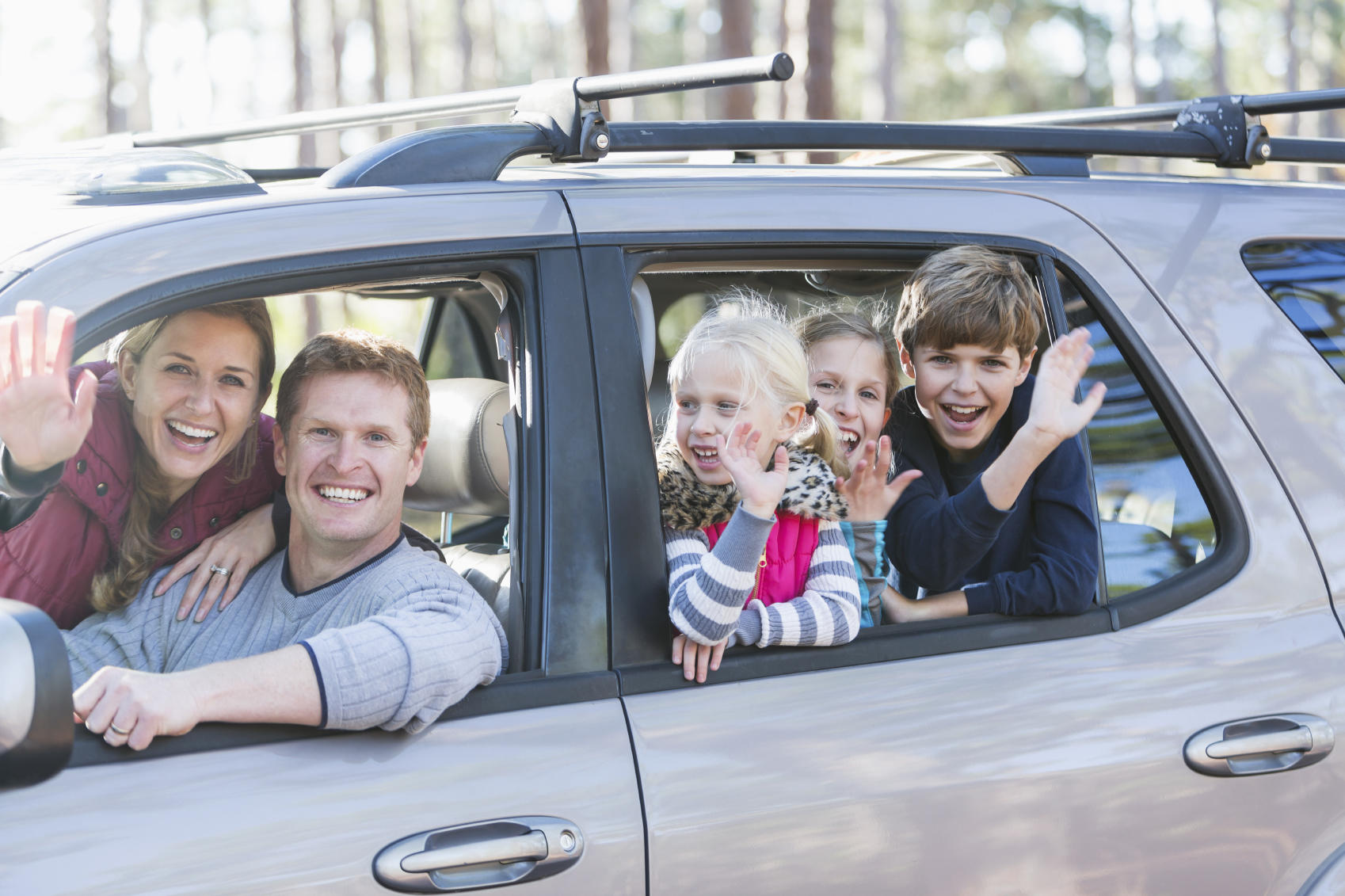 Family with three children in car on road trip