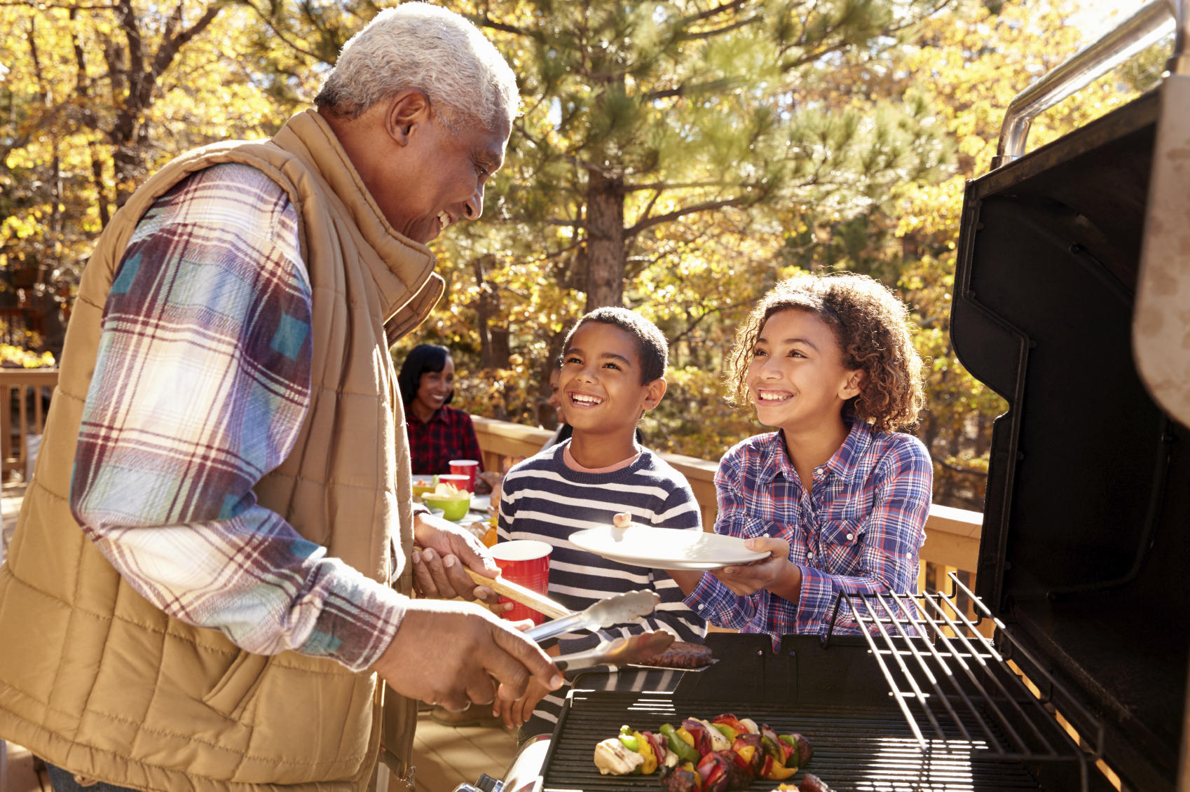 Grandparents With Children Enjoying Outdoor Barbecue