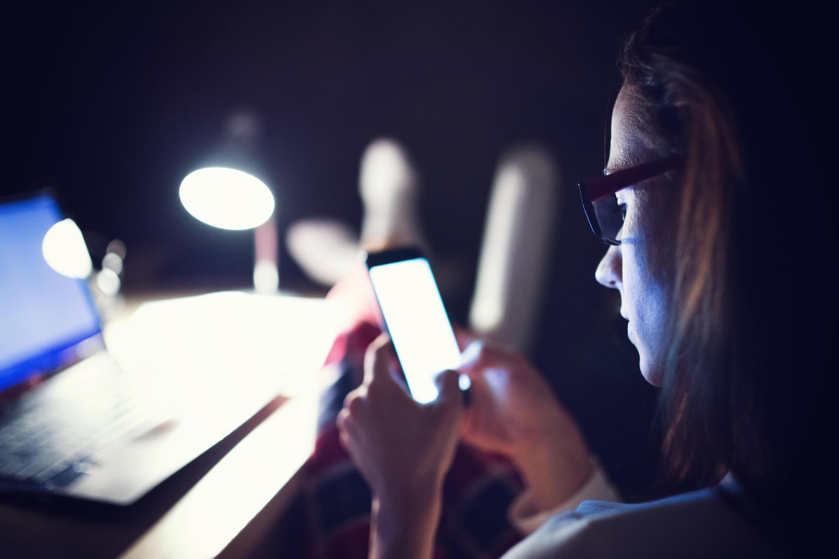 Woman texting at night