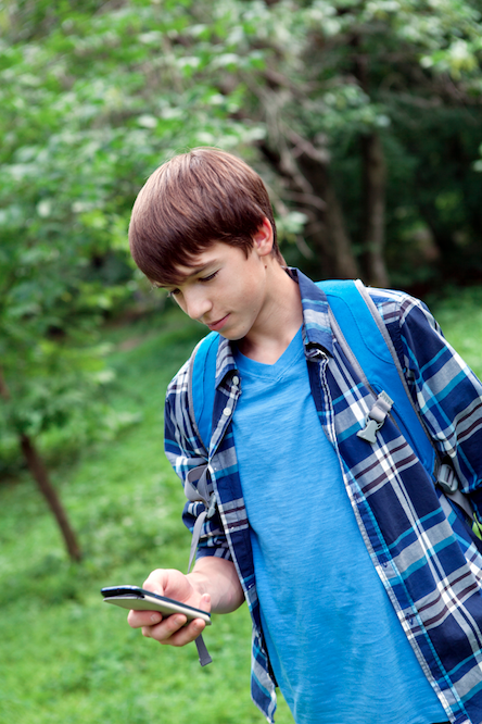Young boy playing on cell phone
