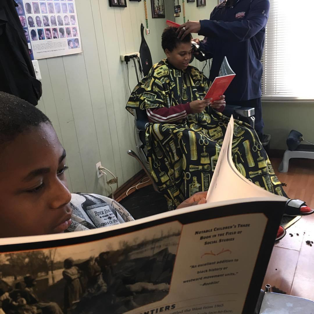 Child reading in barbershop chair