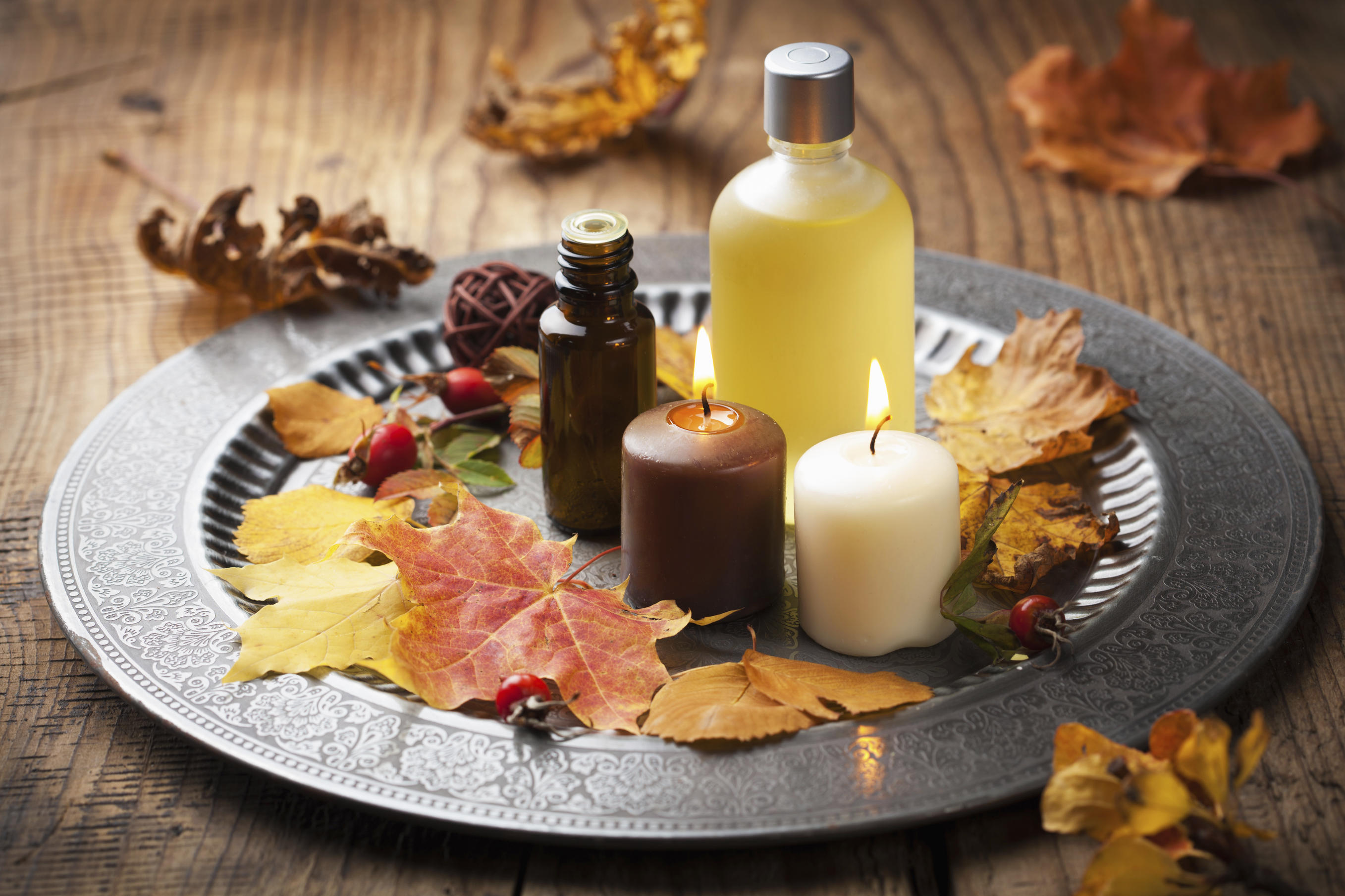 fall leaves, candles and oils on a platter