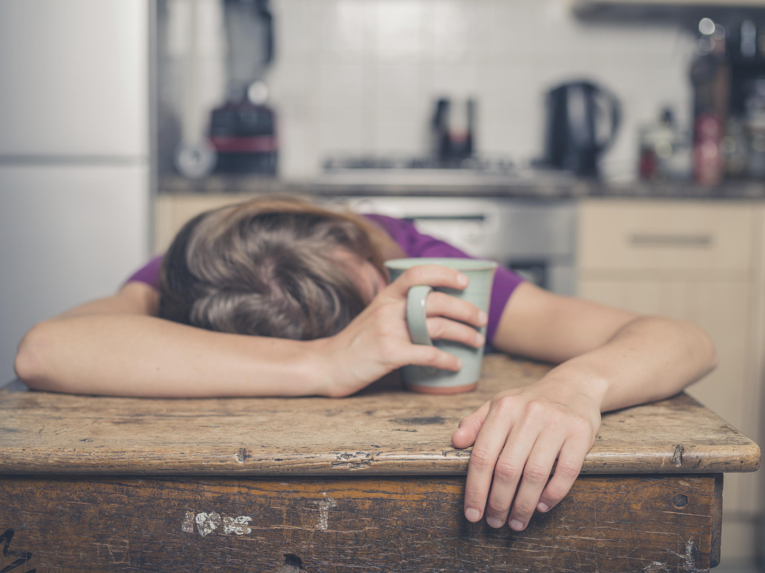 tired women with coffee sleeping on table