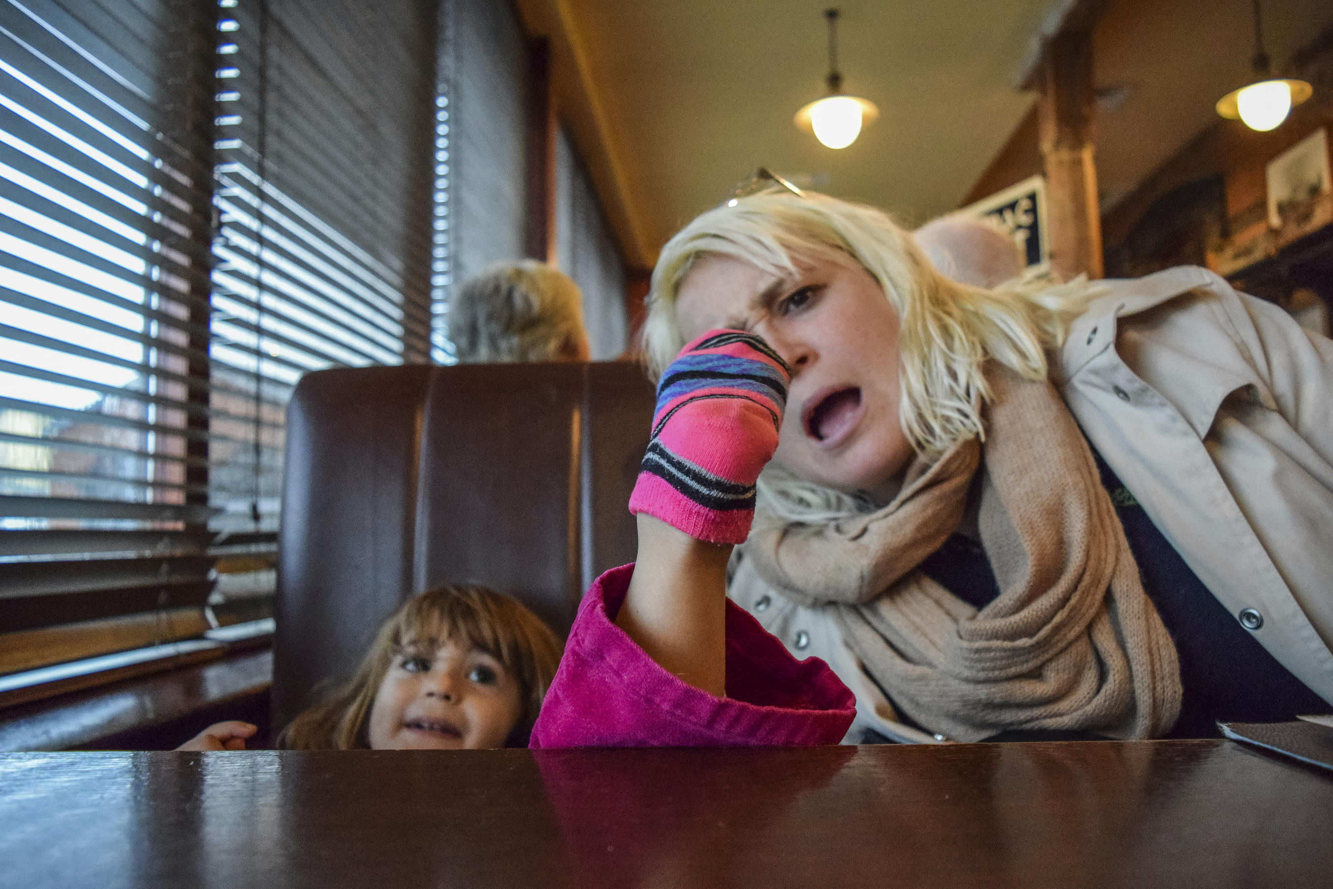 mother and daughter at a table in a restaurant, the child's foot is on the table
