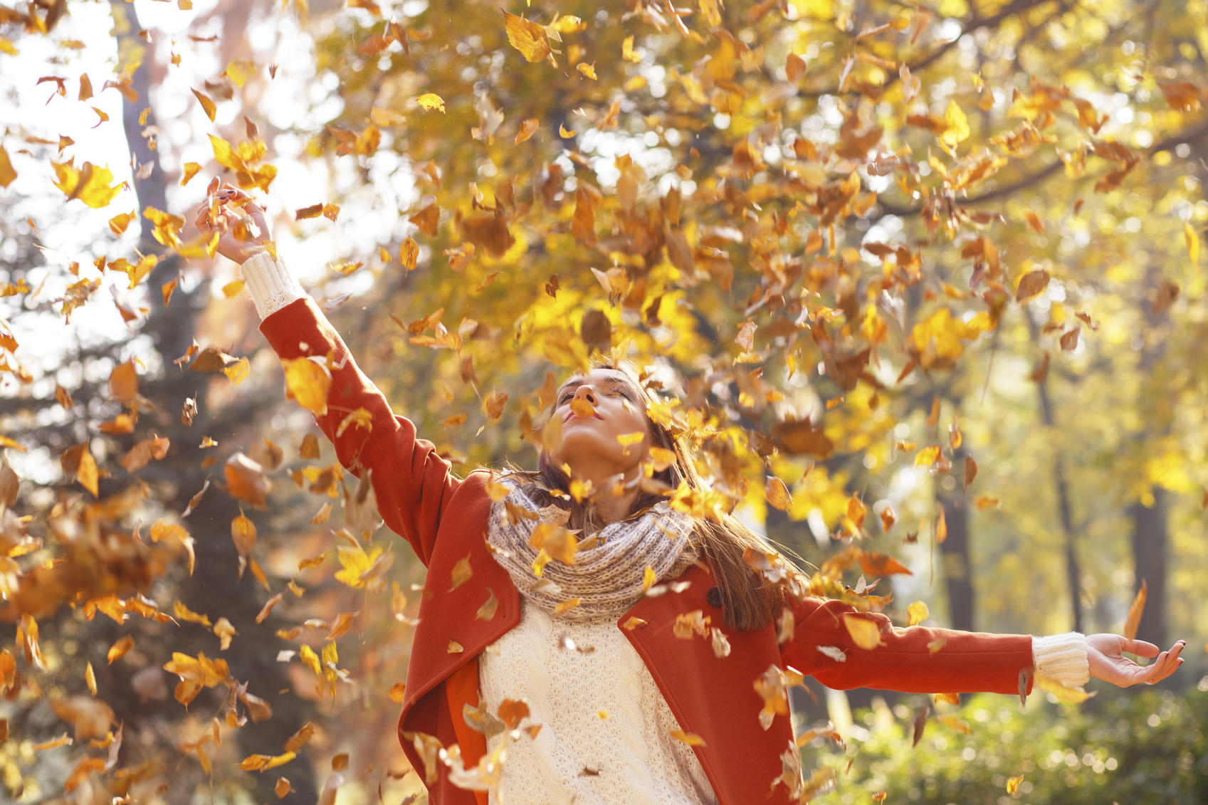 Portrait of a young woman in a park with arms outstretched. She throwing leaves in the air.