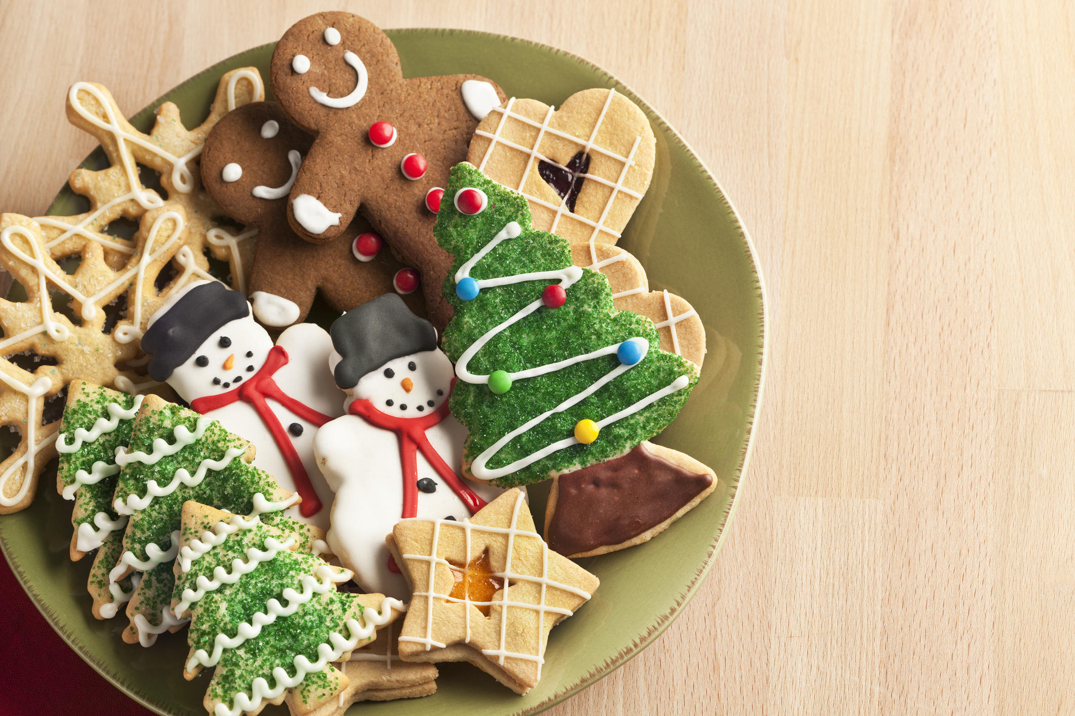 A plate filled with Christmas cookies decorated with frosting and icing for winter holiday celebrations. The baked dessert collection of sweet food features Christmas tree, gingerbread man, snowman, star, heart, and snowflake shapes against the green background of a ceramic plate. The light wooden table area allows for copy space.